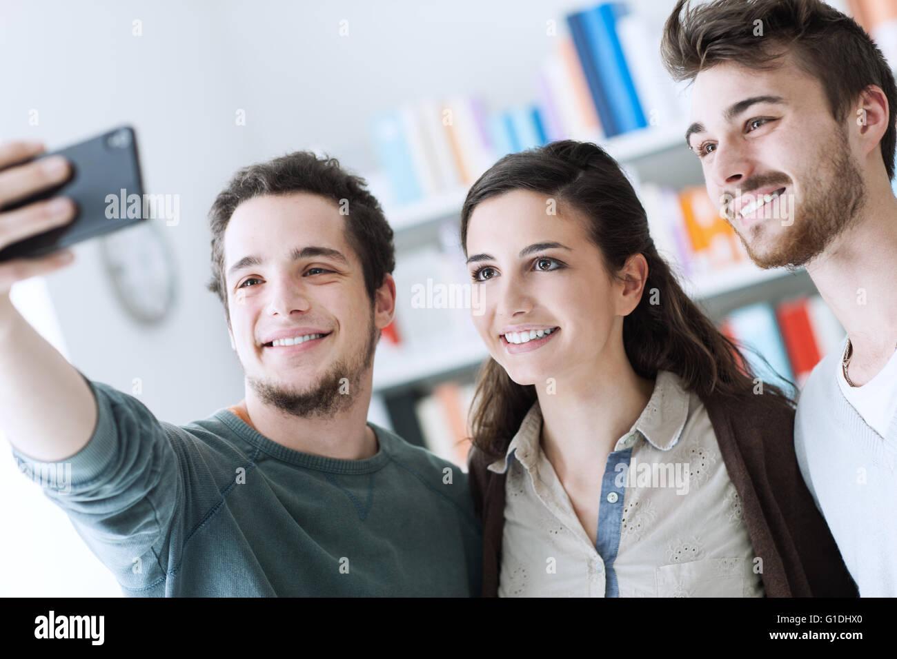 Sorridendo felice adolescenti tenendo selfies con un telefono cellulare, di condivisione e di tecnologia e concetto Immagini Stock