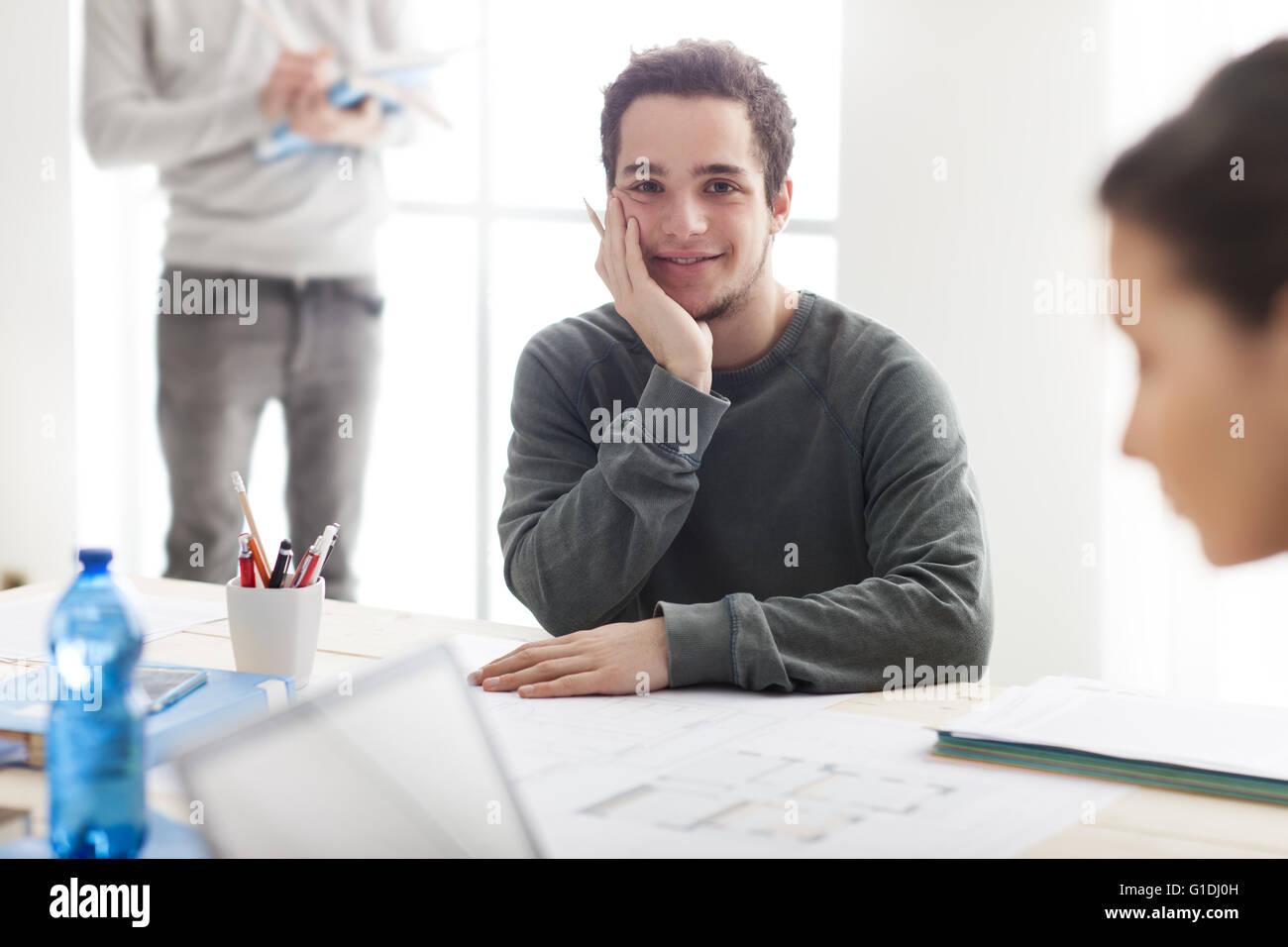 I ragazzi che studiano insieme alla scrivania, uno studente sorride alla telecamera e tenendo una matita, egli sta Immagini Stock