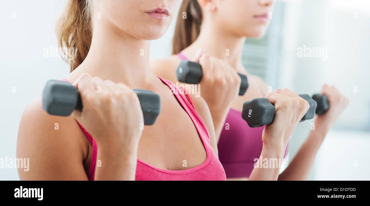 Certi giovani donne che esercitano e il sollevamento pesi in palestra con pesi, allenamento e concetto di fitness Foto Stock