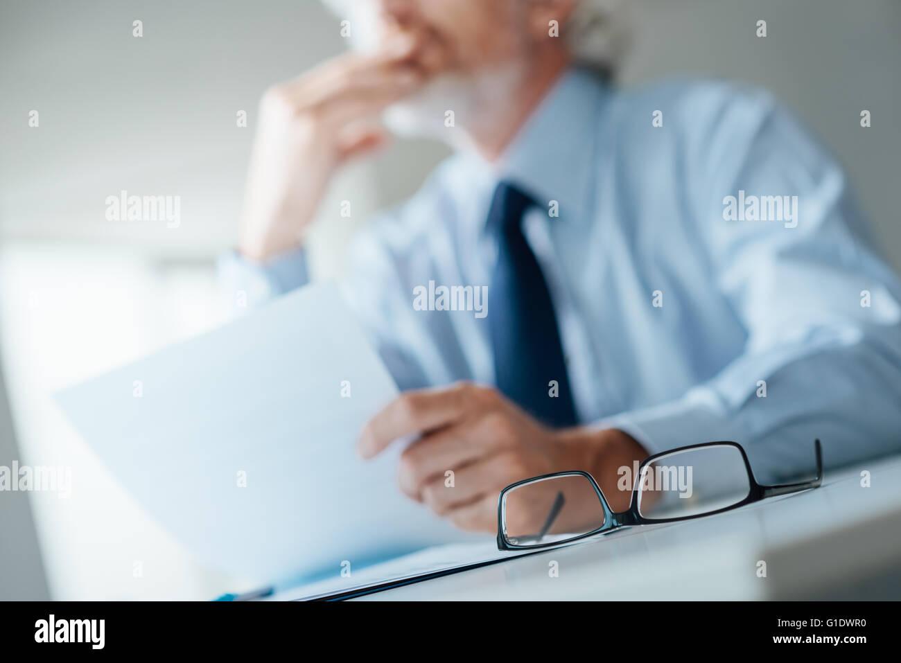 Malinconici imprenditore con mano sul mento che guarda lontano e in possesso di un documento, il fuoco selettivo Immagini Stock