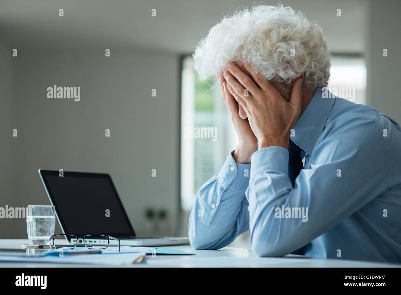 Esaurito imprenditore con testa in mani seduto alla scrivania in ufficio, guasto e concetto di depressione Immagini Stock
