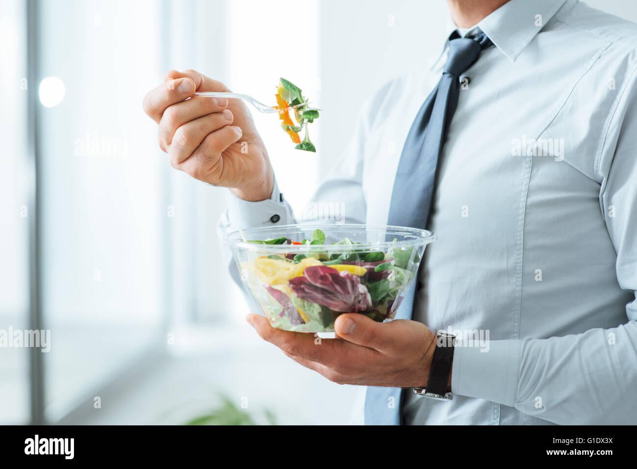 Imprenditore avente un insalata di verdure per pranzo, sana alimentazione e corretto stile di vita concetto, irriconoscibile Immagini Stock