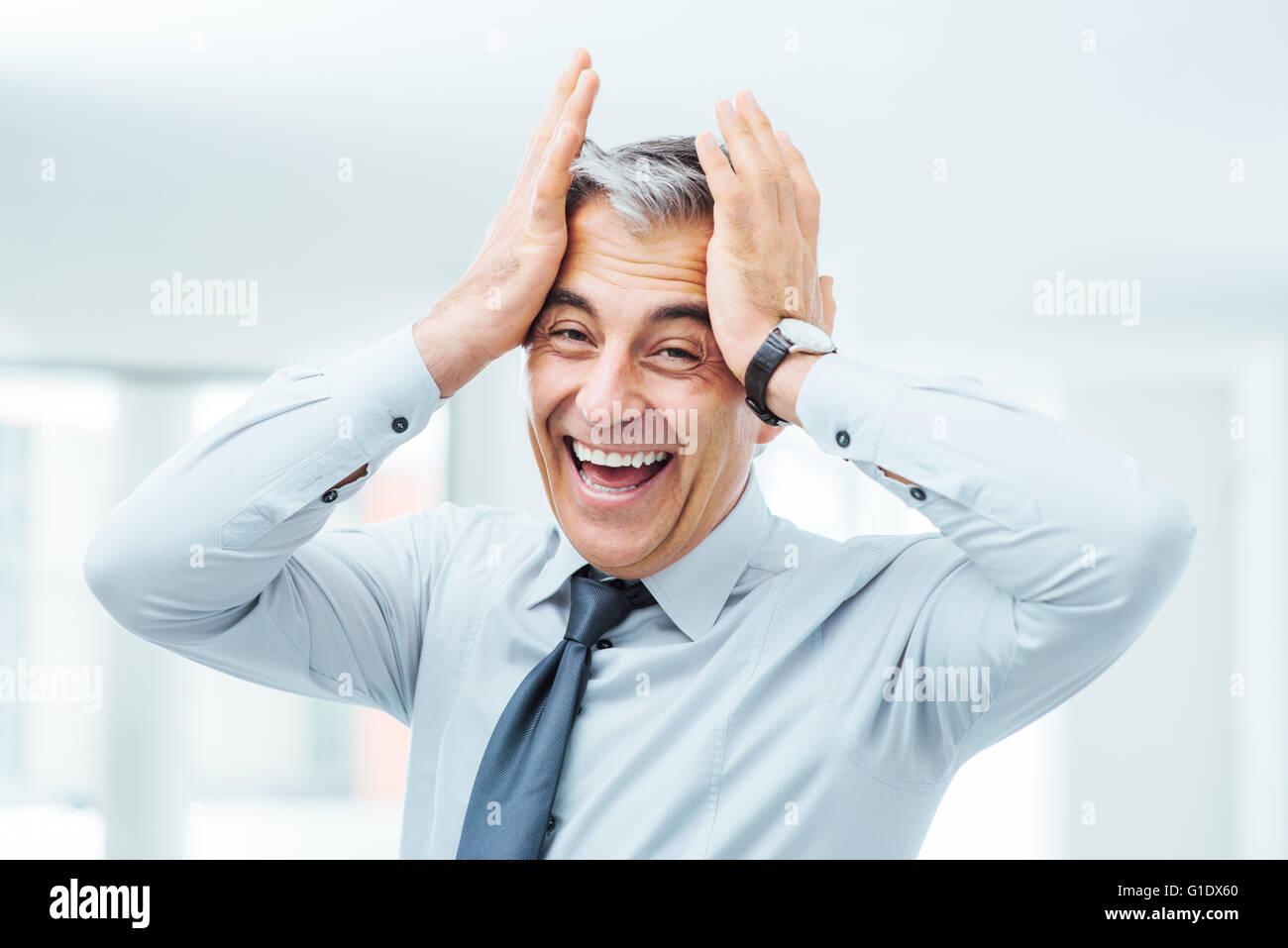 Allegro imprenditore negligente ridendo e toccando il suo fronte Immagini Stock
