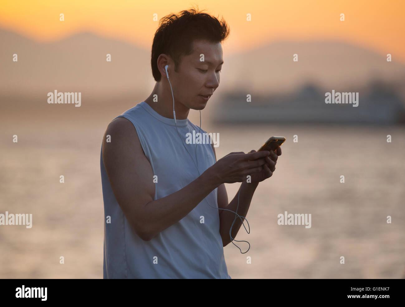 Il controllo della posta elettronica sul telefono, tramonto, Seattle, Puget Sound, Washington Immagini Stock