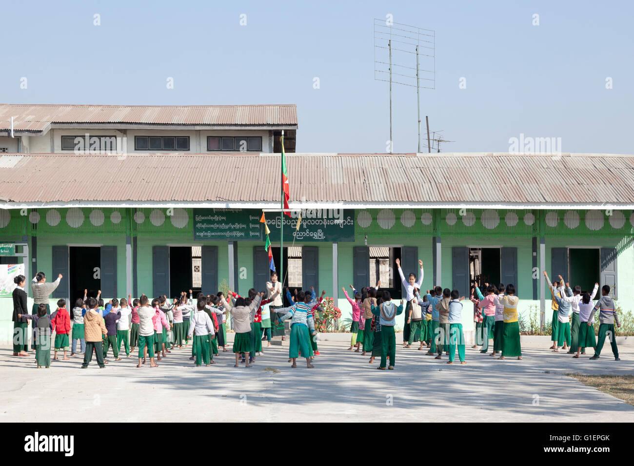 Prima di classe, il pupillo di allenamento fisico in una scuola primaria di Nyaungshwe (Myanmar). La culture physique Immagini Stock
