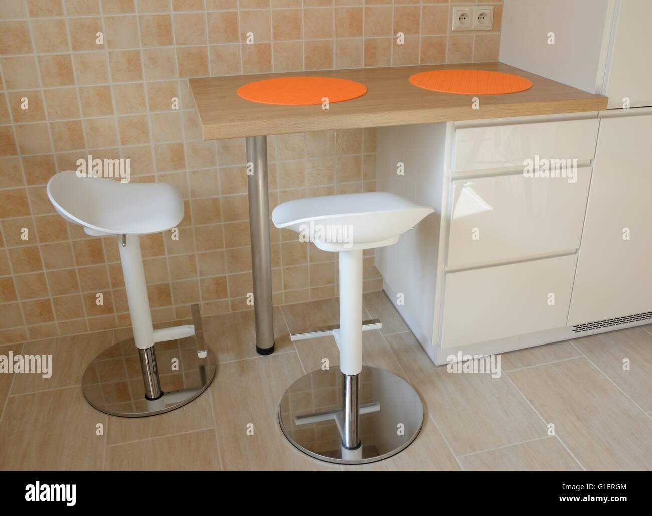 Due sgabelli girevoli e cucina piccola tabella con orange tablemats