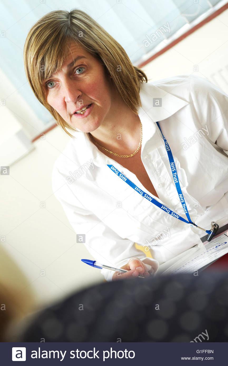 Regno Unito femmina bianca consulente sanitario / medico parla al paziente durante la consultazione in un affollato Immagini Stock