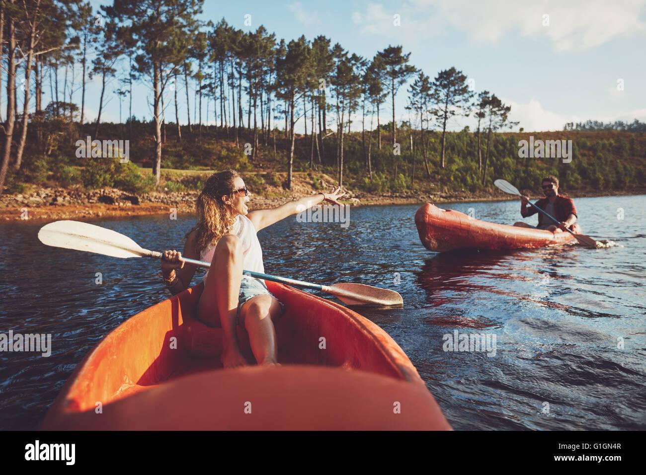 Coppia giovane canottaggio sul lago. Giovani kayakers godendo una giornata al lago. Immagini Stock