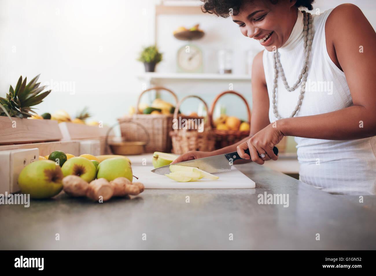 Attraente giovane donna sminuzzare frutta fresca per frullato. Lavoro femminile al bar dei succhi. Immagini Stock