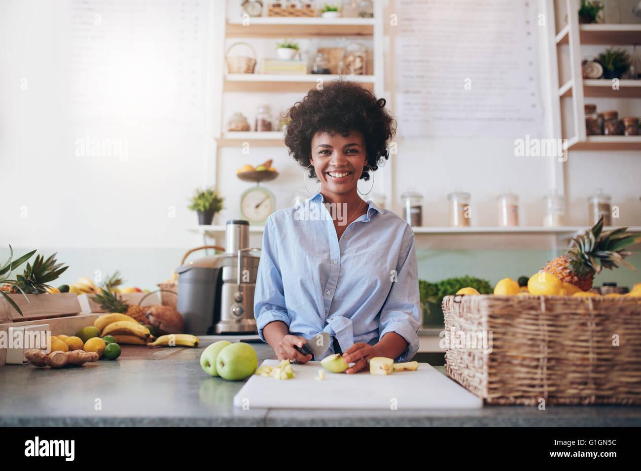 Ritratto di giovane e bella donna africana in piedi dietro il bancone bar e trinciatura di frutta fresca. La donna Immagini Stock