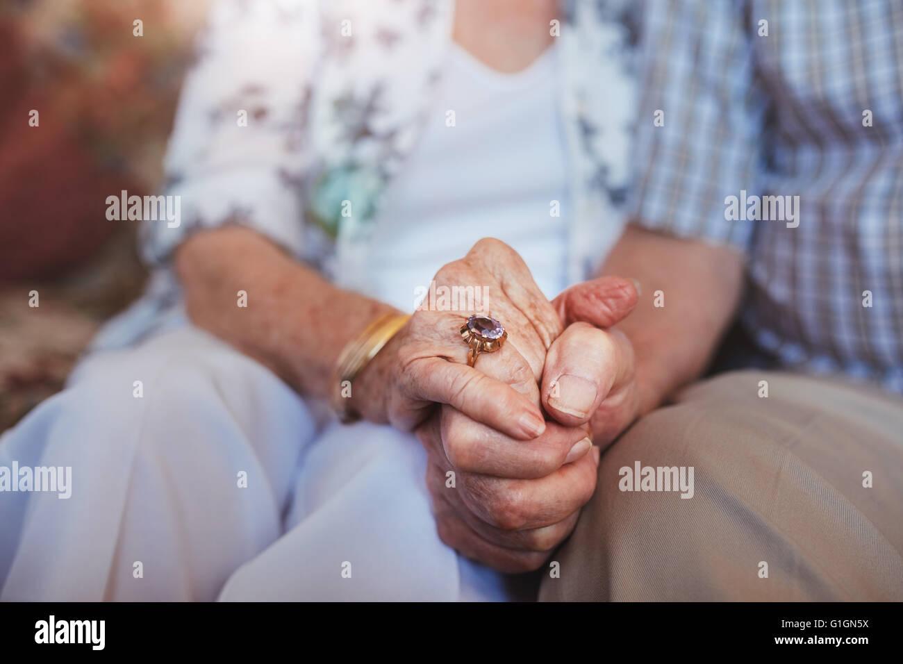 Ritagliato colpo di coppia di anziani tenendo le mani seduti insieme a casa. Concentrarsi sulle mani. Immagini Stock