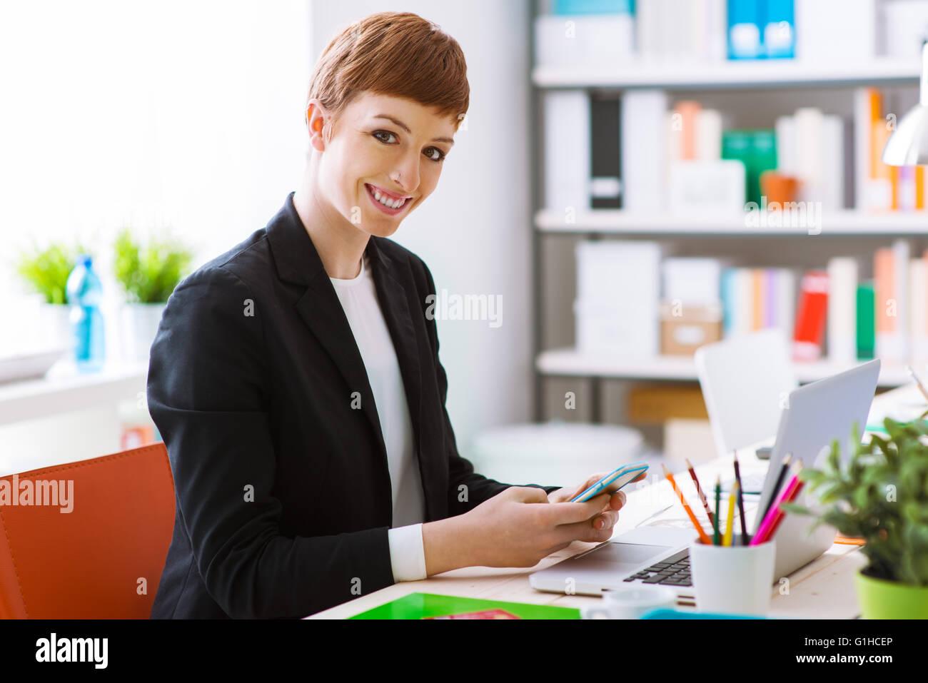 Successo imprenditrice fiducioso nel suo ufficio utilizzando un telefono intelligente, ella è sms e utilizzando Immagini Stock
