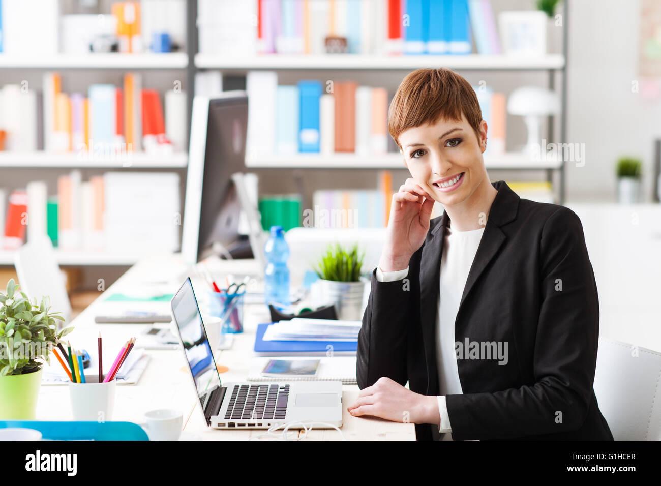 Fiducioso Imprenditrice di successo seduto alla scrivania in ufficio e lavorare con un portatile, è sorridente Immagini Stock