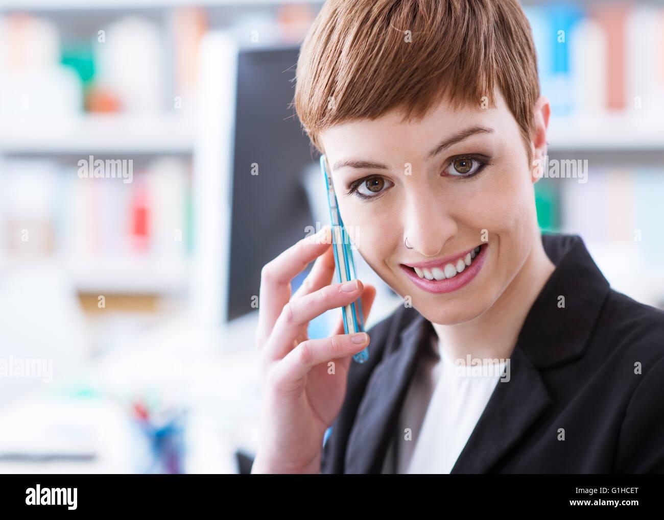 Sorridente fiducioso imprenditrice sul telefono, Ella è chiamata con uno smart phone Immagini Stock