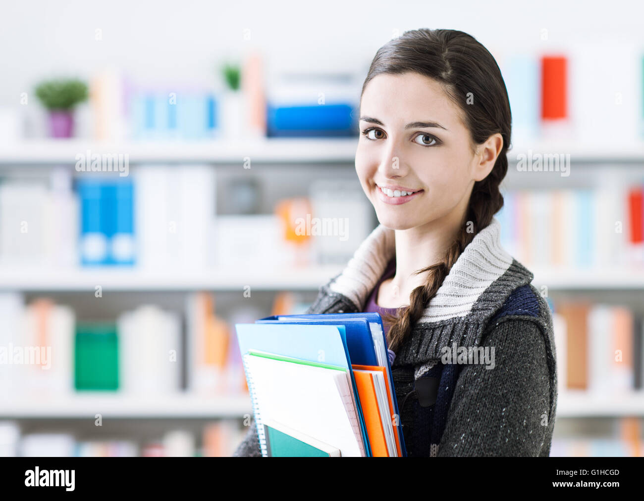 Sorridente giovane studente ragazza in posa nella biblioteca della scuola, ella è in possesso di notebook e Immagini Stock