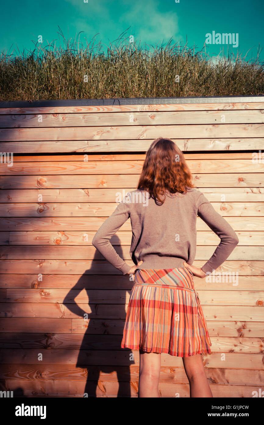 Una giovane donna è in piedi in un giardino al di fuori di una cabina in legno ed è la ricerca di Immagini Stock
