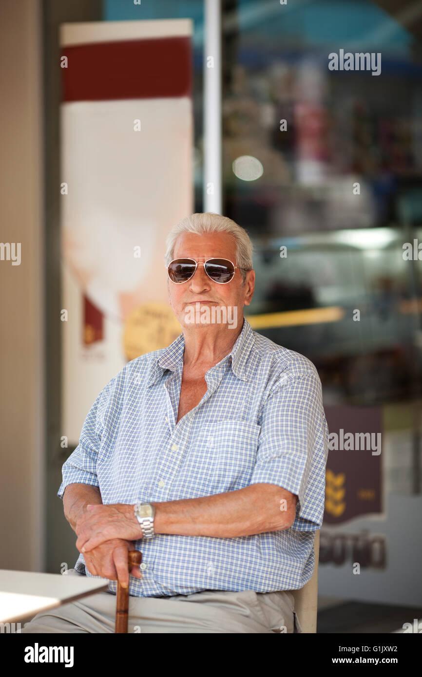 Uomo anziano in attesa in una tabella al di fuori di un negozio Immagini Stock