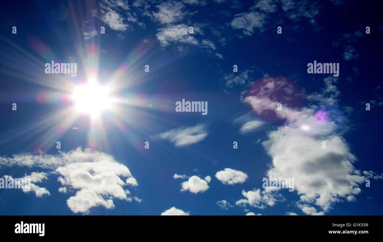 Deserto dei raggi solari in presenza di striature nel cielo blu con nuvole frammentarie Immagini Stock