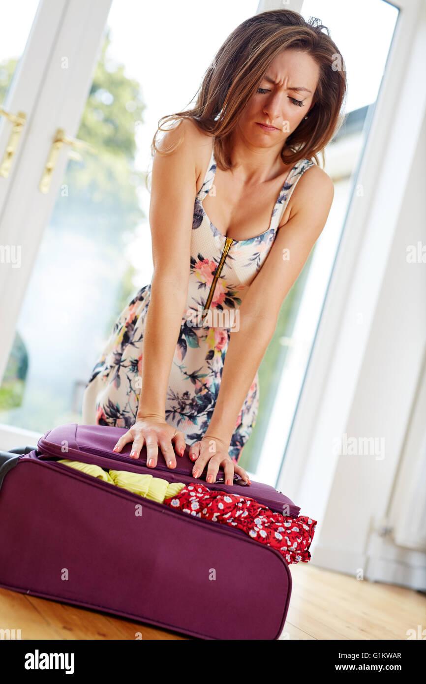 Ragazza lottando per chiudere la valigia Immagini Stock