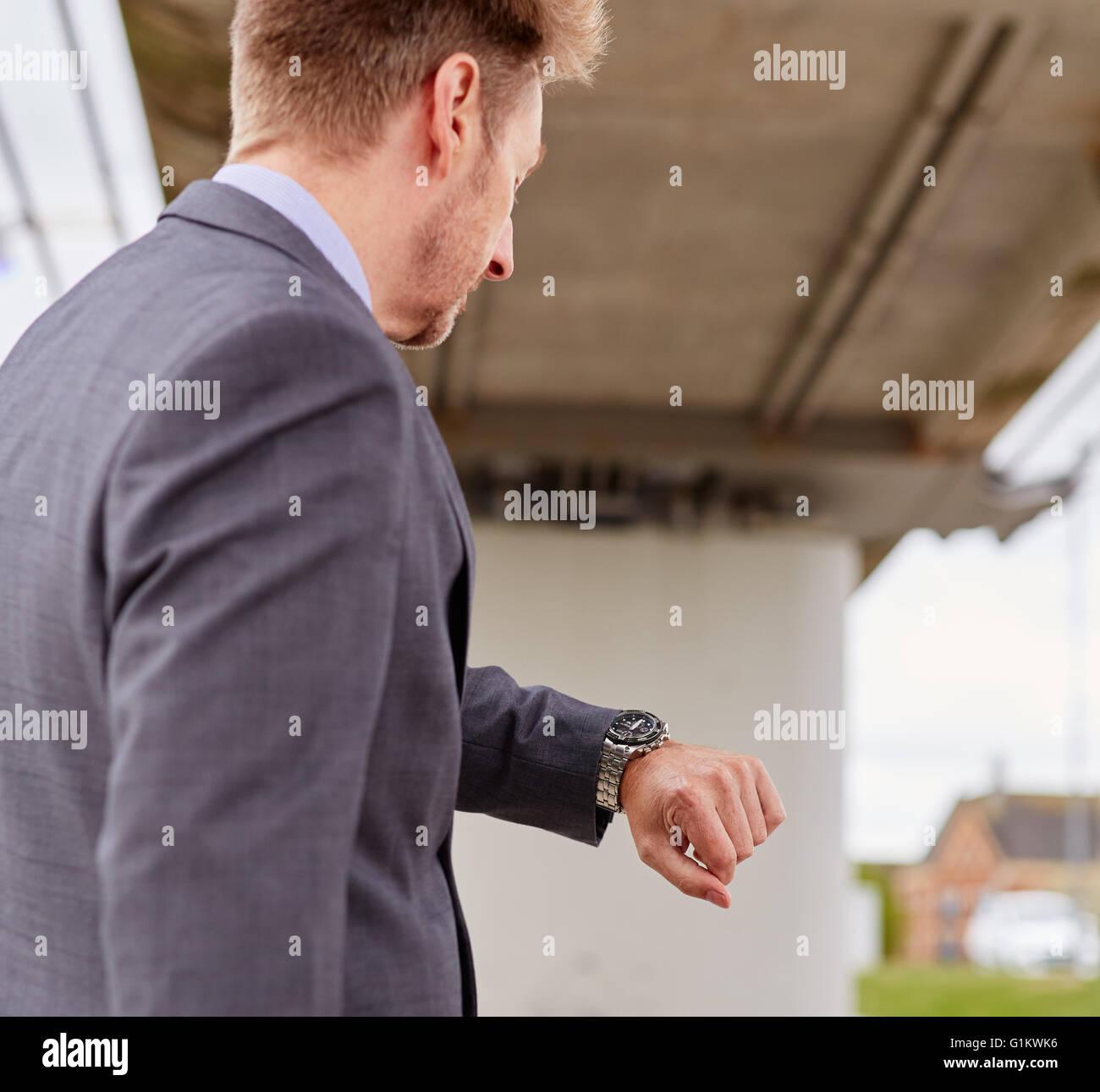 Uomo che guarda il suo orologio correndo per il lavoro Immagini Stock