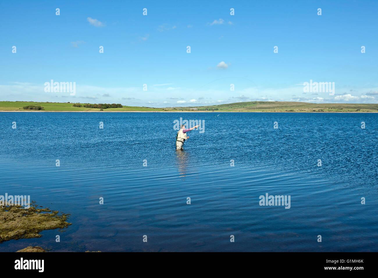 La pesca a mosca sul serbatoio Colliford lago Bodmin Moor Cornwall lone uomo casting con asta sul lago ancora cielo Immagini Stock