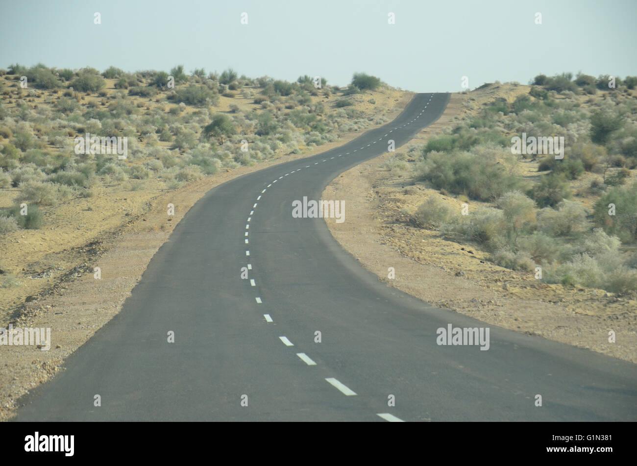 Autostrada verso il confine Indo-Pak, deserto di Thar, Rajasthan, India Immagini Stock