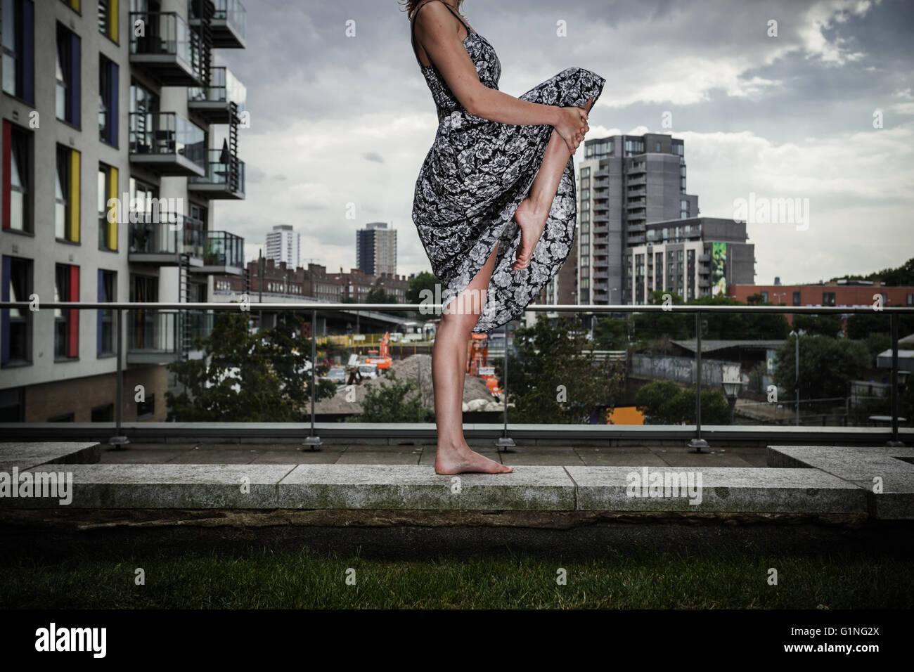 Una giovane donna che indossa un abito è alzando la gamba come lei è in piedi su un tetto alto Immagini Stock