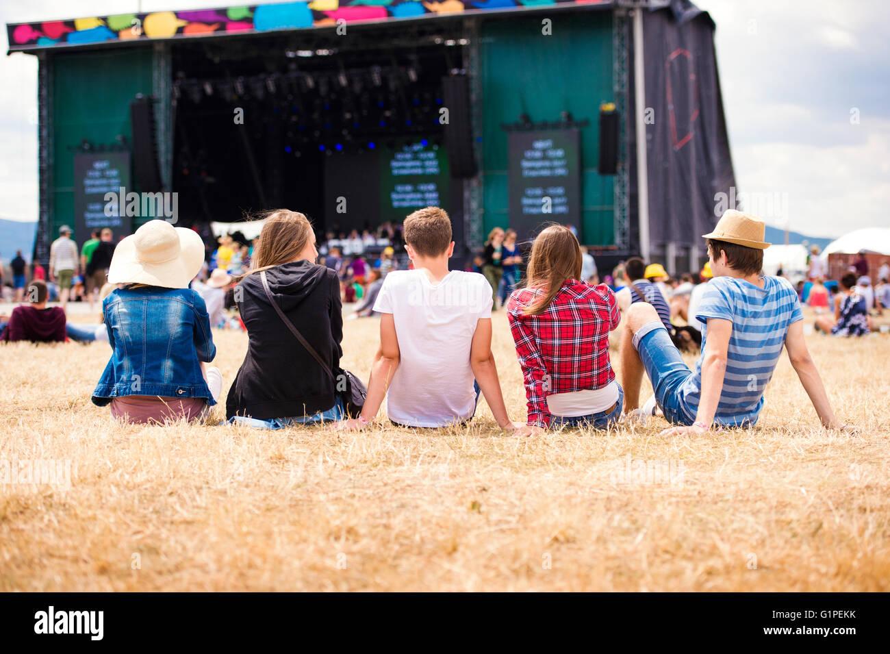 Gli adolescenti, i festival estivi di musica, seduti nella parte anteriore della fase Immagini Stock