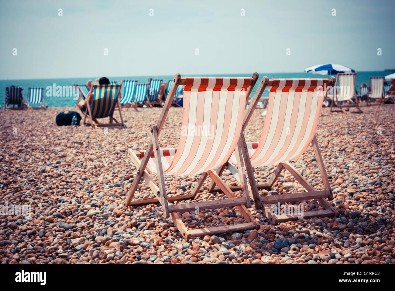 Due sedie a sdraio sulla spiaggia di ghiaia Foto Stock
