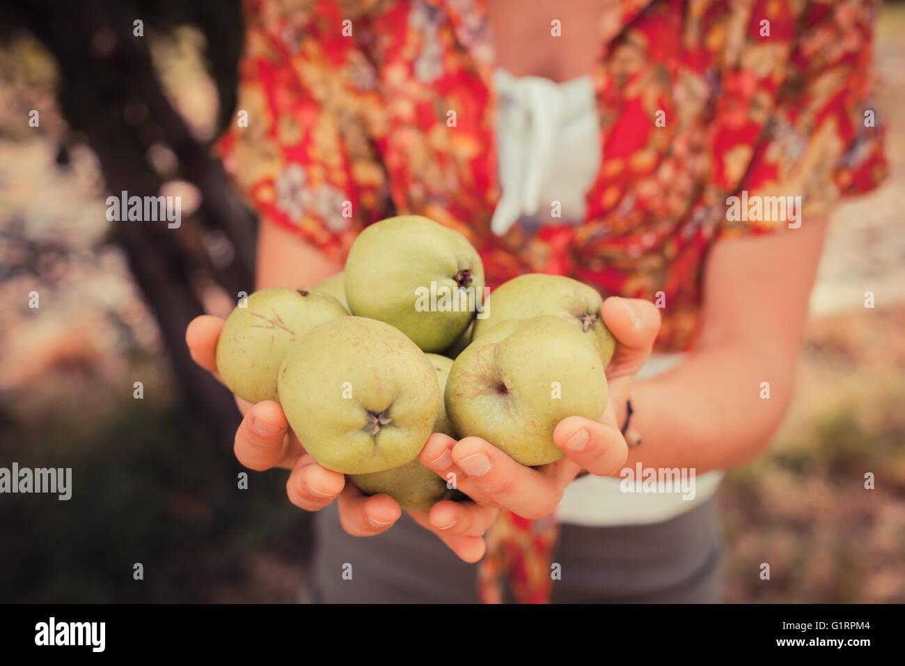 Una giovane donna è in piedi sotto un albero ed è in possesso di un mucchio di mele Immagini Stock