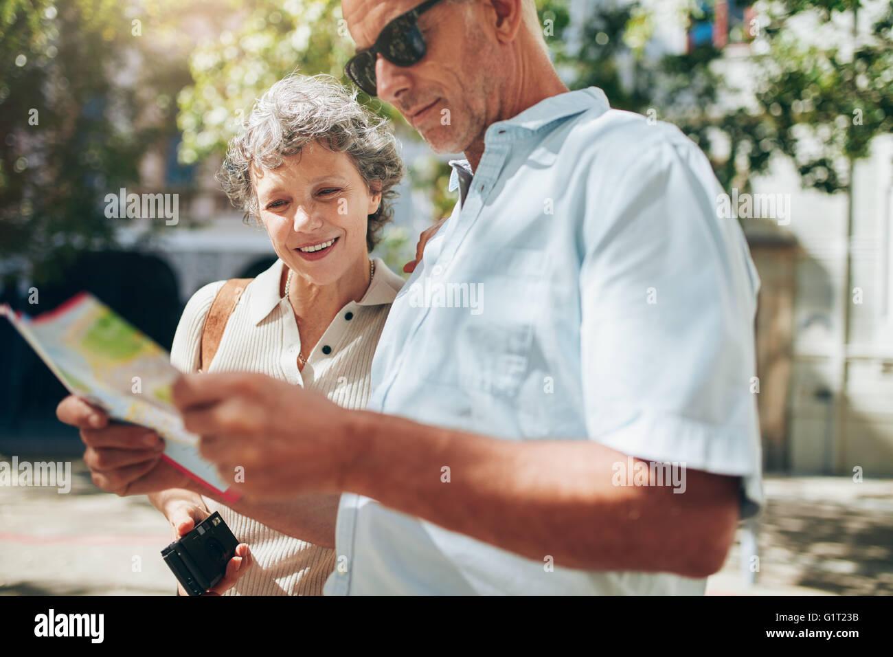 Immagine ravvicinata di senior attivo su una vacanza la lettura di una mappa della città. Uomo maturo e la Immagini Stock