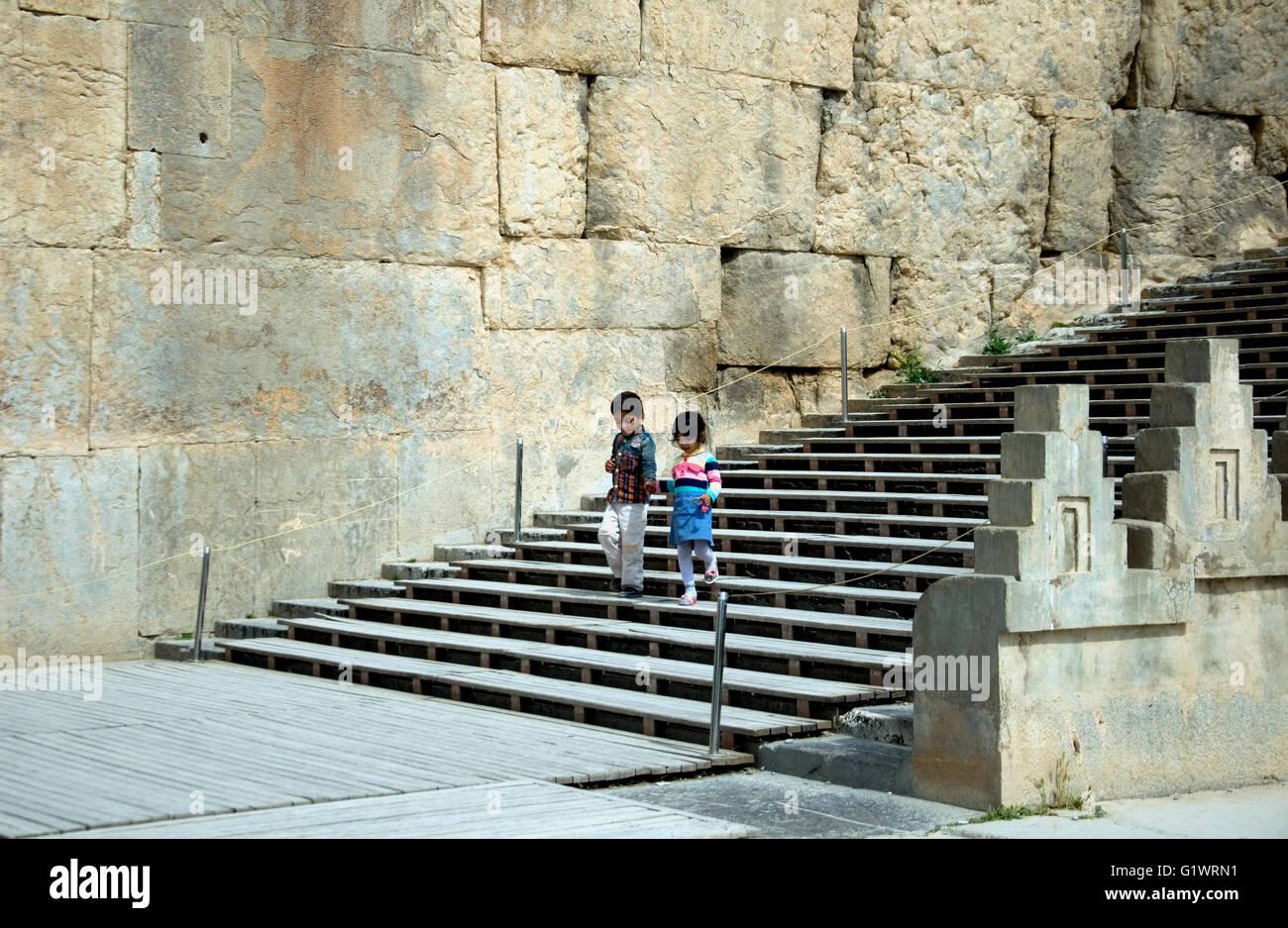 A Persepoli, all'Iran il più grande sito storico, due bambini scendere dalla grande scala vicino all'ingresso Immagini Stock