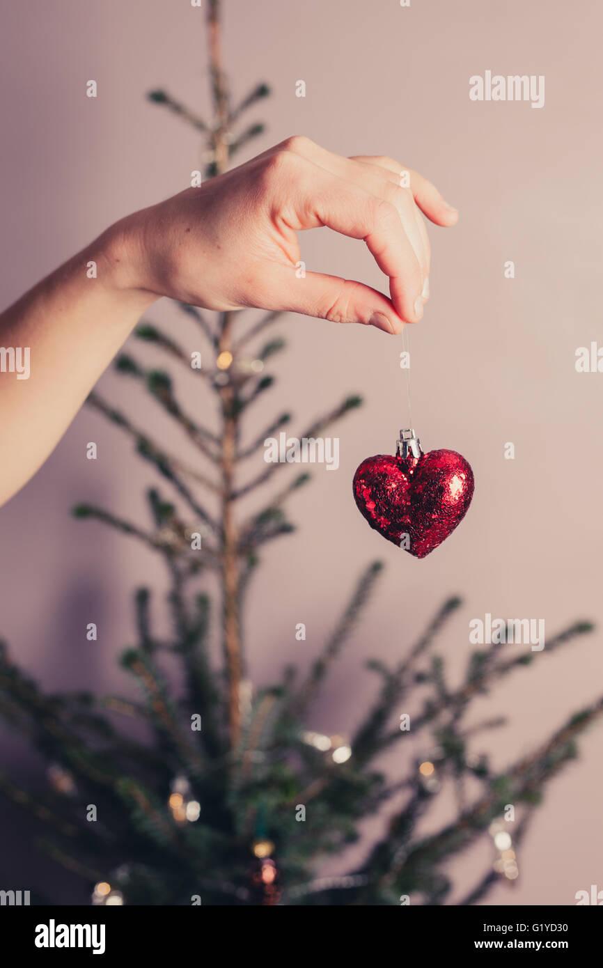 Una mano è in possesso di una Decorazione cuore per mezzo di un albero di natale Immagini Stock