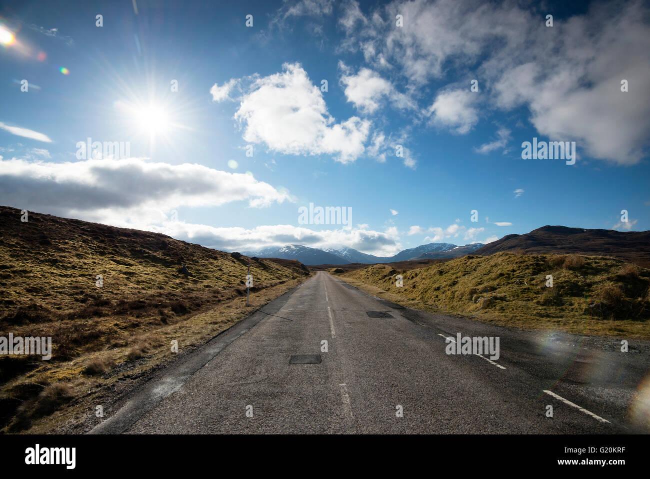 Soffici nuvole bianche e infinite strada aperta sulla A832 nell'estremo nord-ovest della Scozia, Regno Unito Foto Stock