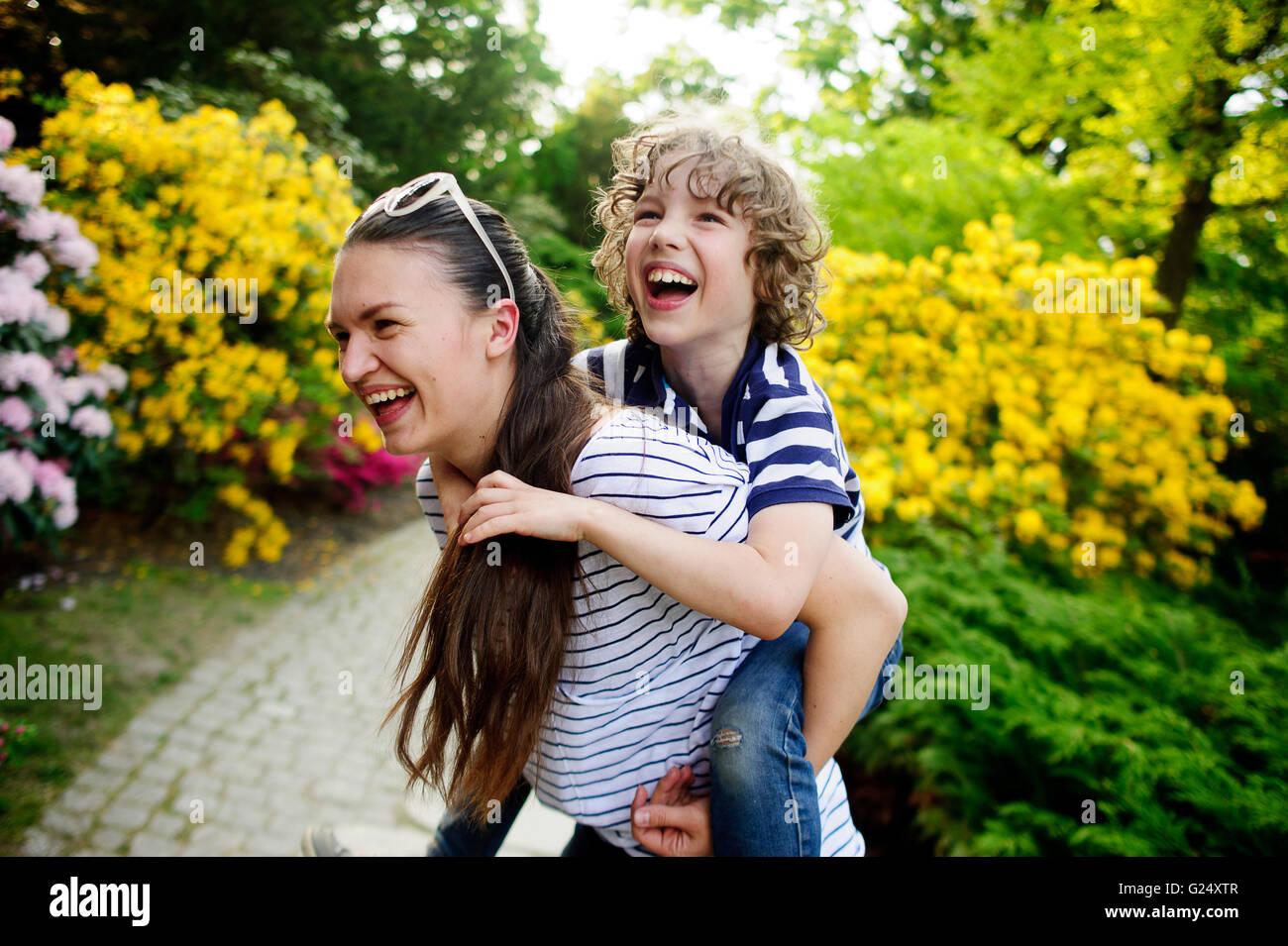 Donna giovane ragazzo ha dato un piggyback ride Immagini Stock