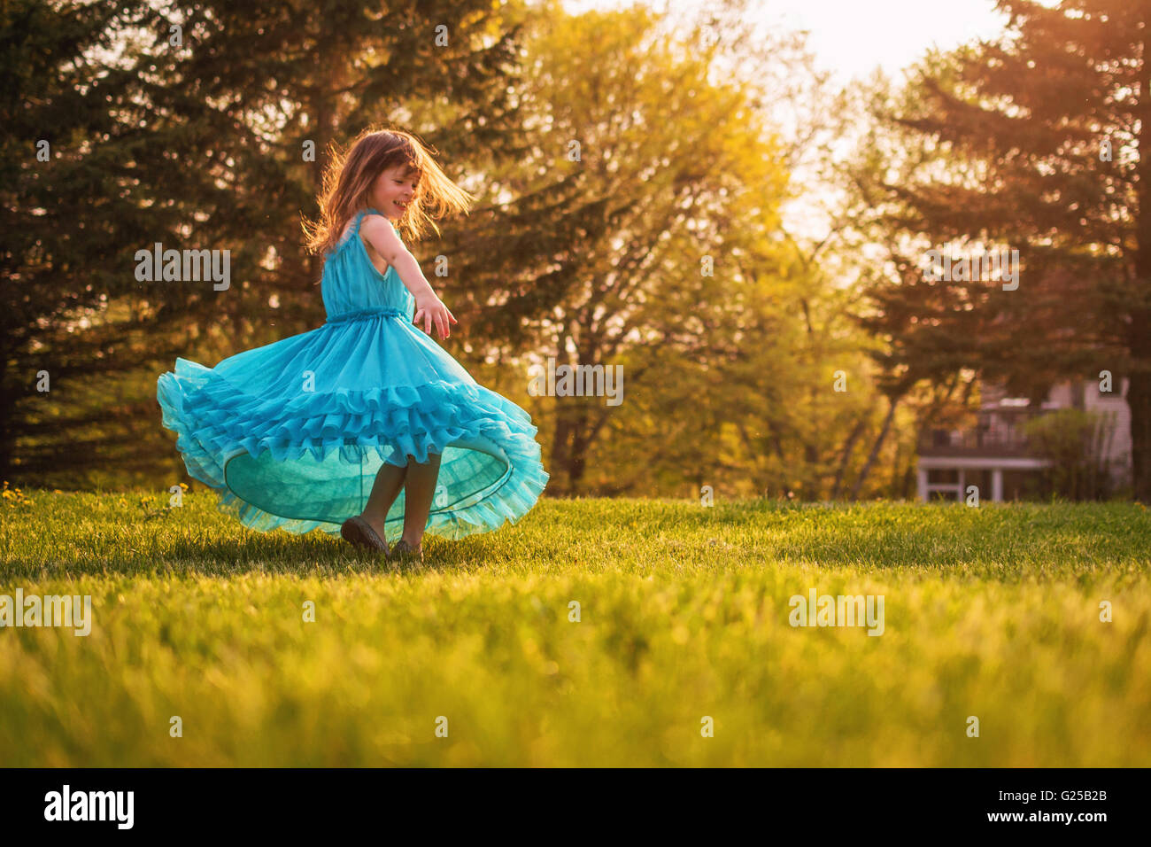 Ragazza nel giardino di girare intorno a un abito Foto Stock