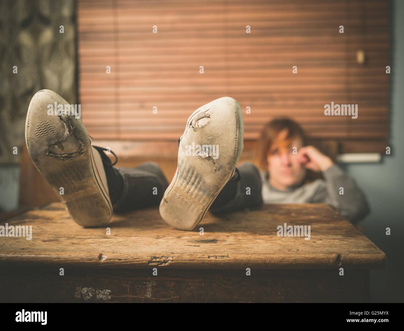 Una giovane donna che indossa usurati scarpe è in appoggio i suoi piedi su un tavolo a casa Foto Stock