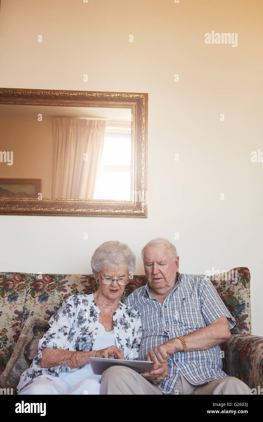 Indoor verticale colpo di coppia in pensione a casa utilizzando la tavoletta digitale. Senior uomo caucasico e donna Immagini Stock