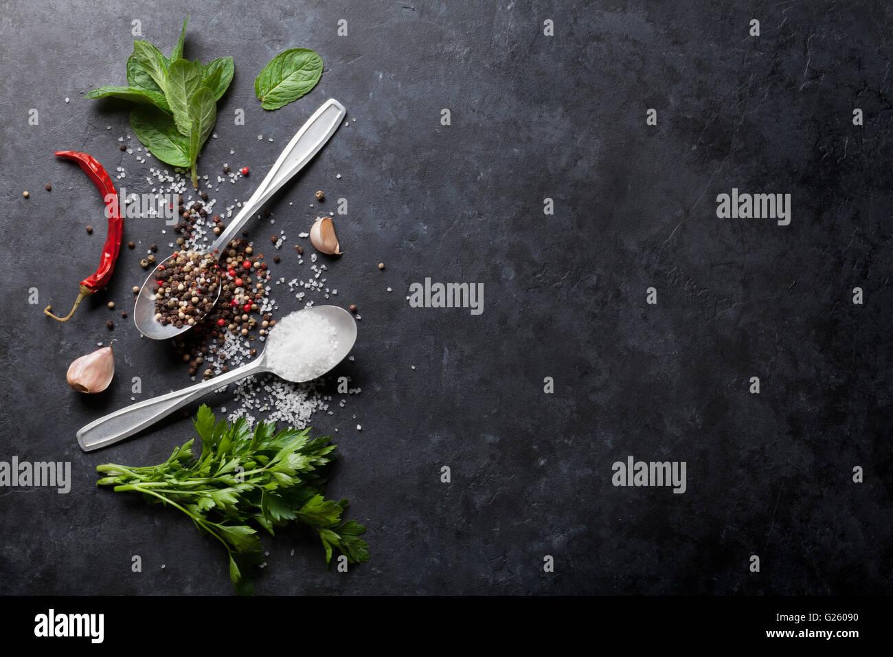 Nero, bianco e pepe rosso sale e spezie in cucchiaio. La menta e il prezzemolo erbe aromatiche. Vista da sopra con Immagini Stock