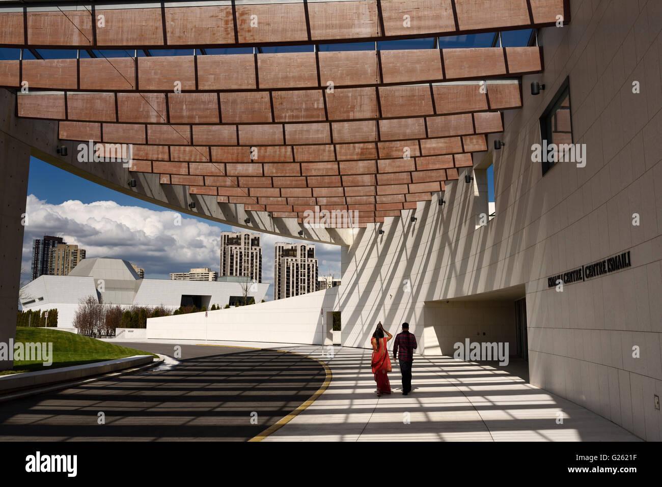 Giovane a piedi dall'entrata di Ismaili Center con Museo Aga Khan a Toronto Immagini Stock