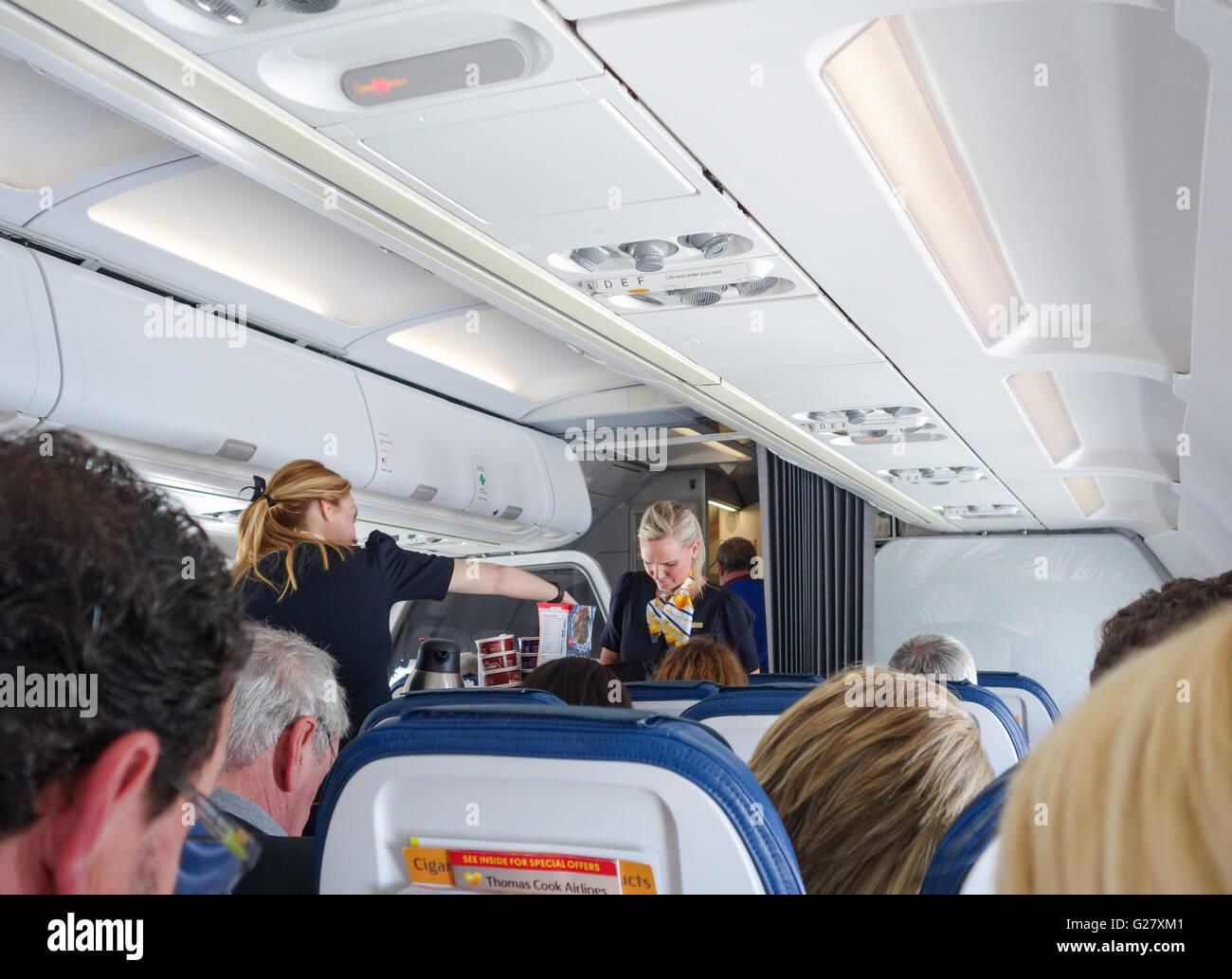 Hostess di aria che serve cibo e bevande a bordo della Thomas Cook Airlines Airbus A321 Immagini Stock