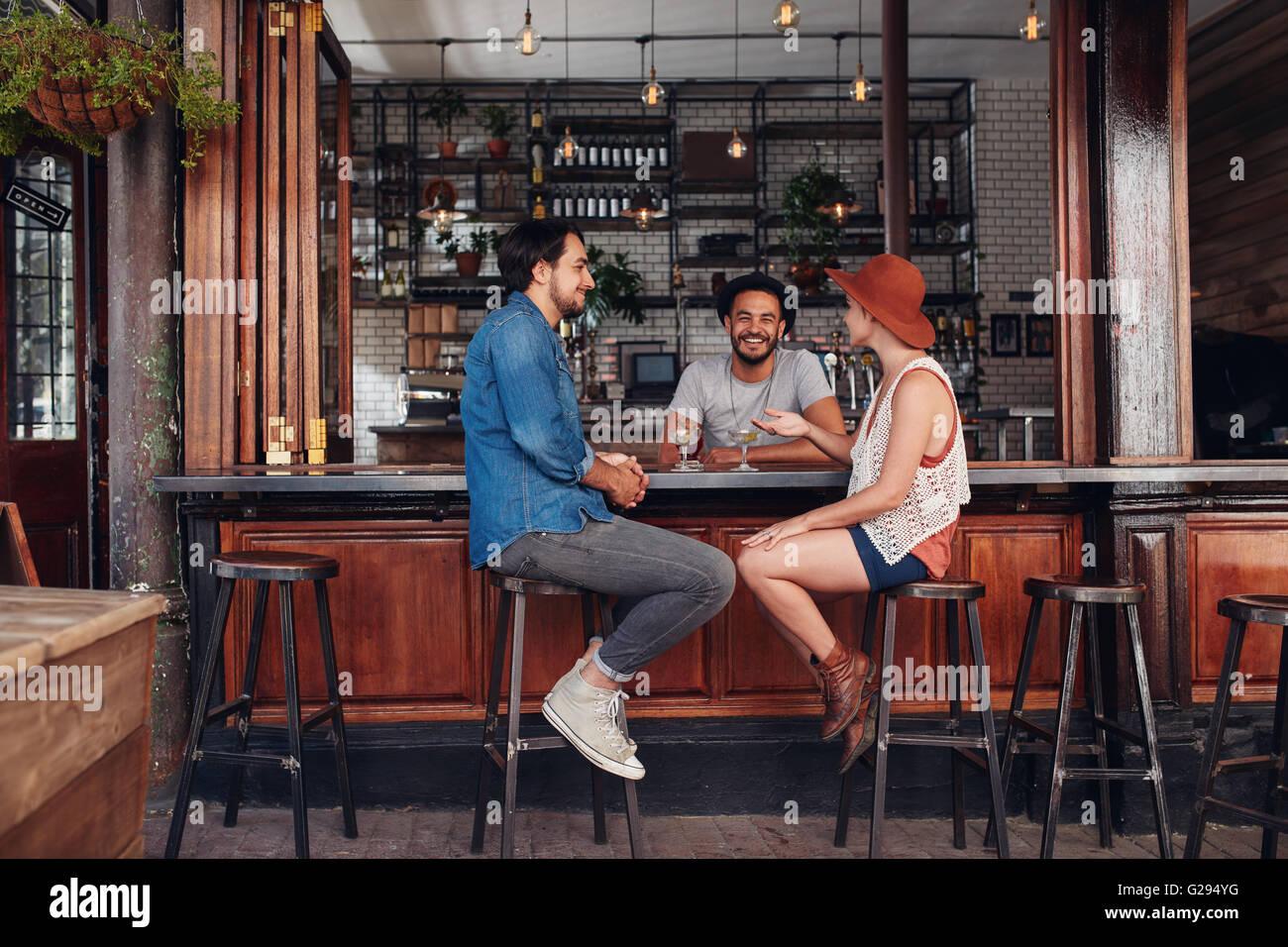 Un gruppo di giovani seduti in un caffè e parlare. Giovani uomini e donne riuniti presso il cafe tabella. Immagini Stock