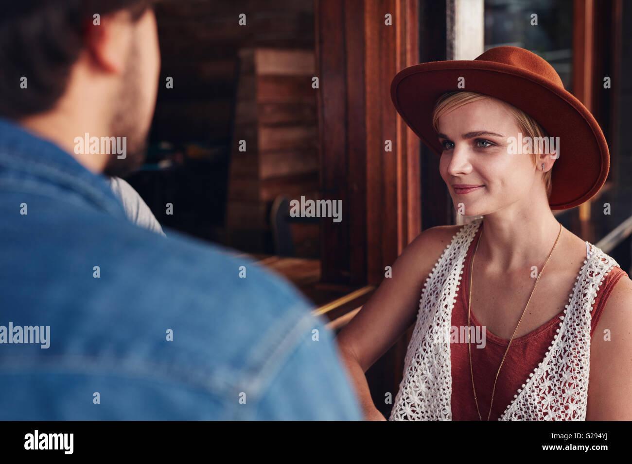 Ritratto di giovane e bella donna seduta in un bar con il suo amico. Immagini Stock