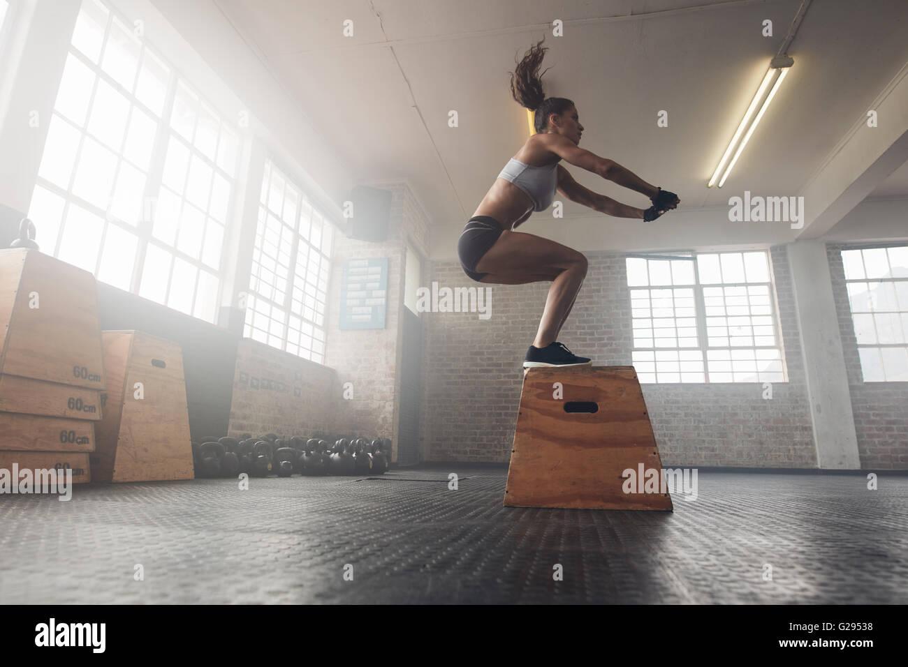 Vista laterale immagine di montare la giovane donna facendo un salto in scatola di esercizio. Donna muscolare facendo Immagini Stock