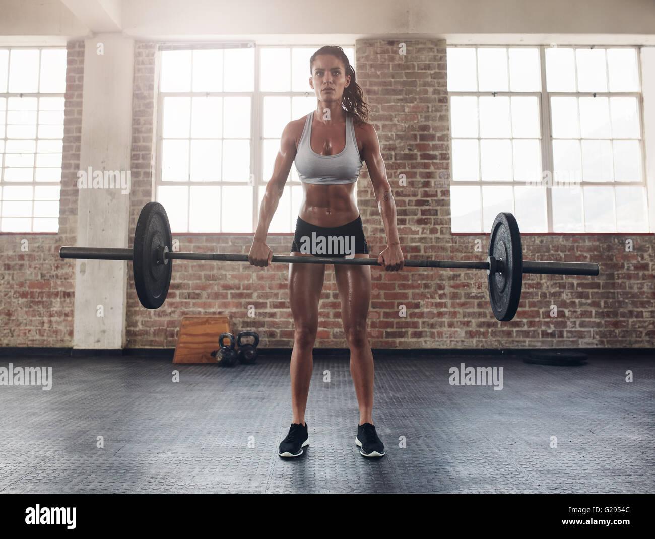 Lunghezza completa immagine di duro giovane donna esercitando con barbell. Determinato atleta femminile di sollevamento Immagini Stock