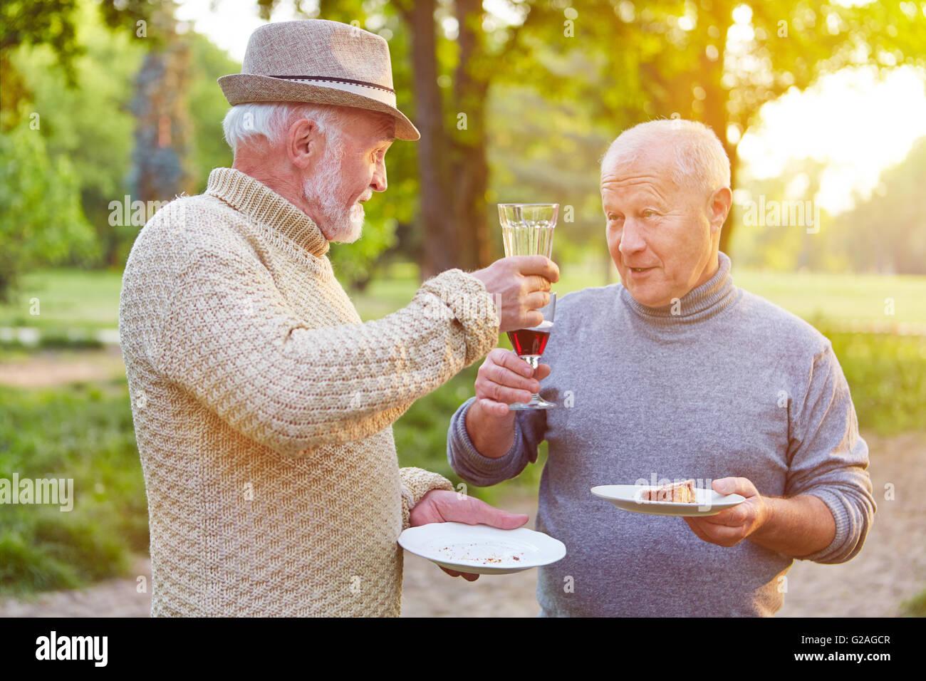 Due alti uomini ad una festa di compleanno tifo con un bicchiere di vino rosso Immagini Stock