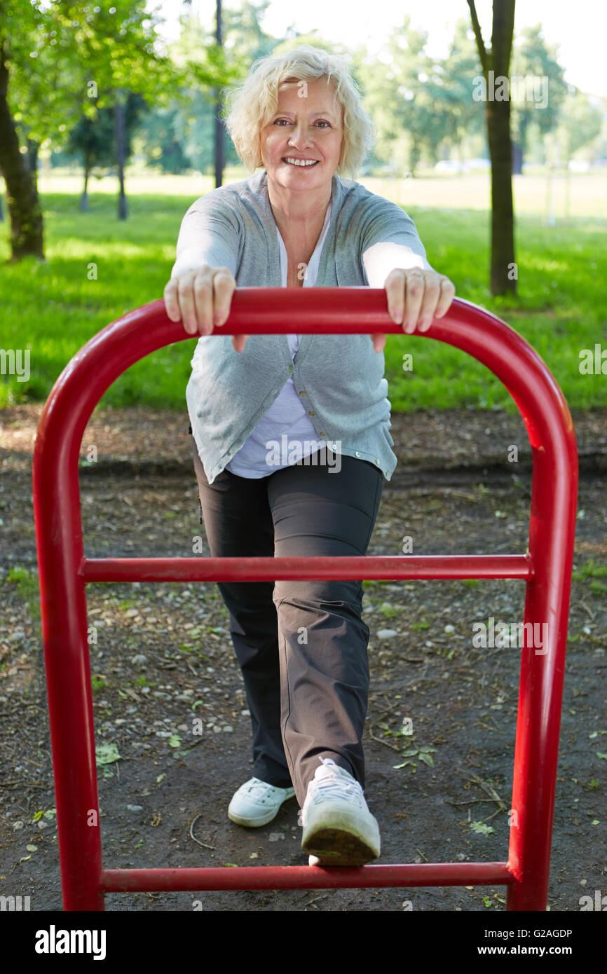 Attiva donna senior esercitando su un mantenersi trail in estate Immagini Stock
