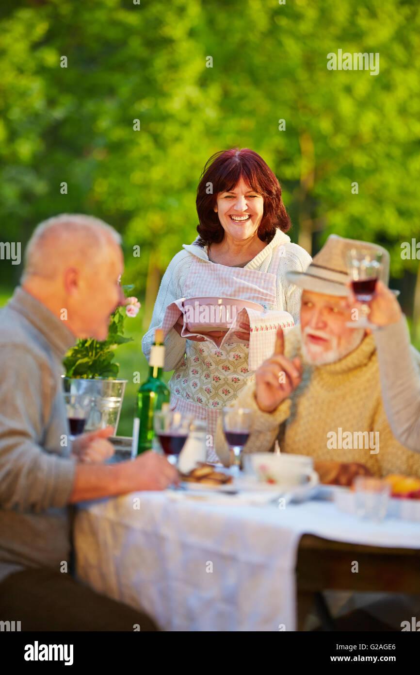 Felice senior amici festeggia il compleanno in un giardino con torta e vino rosso Immagini Stock