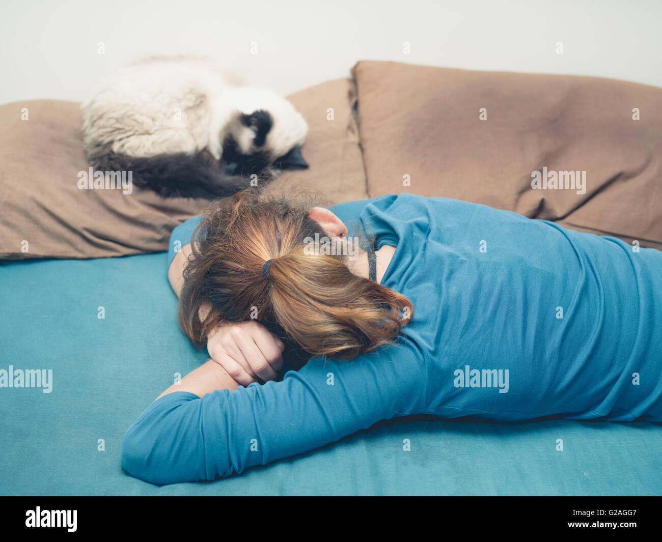 Una giovane donna è dormire in un letto con un gatto accanto a lei Immagini Stock