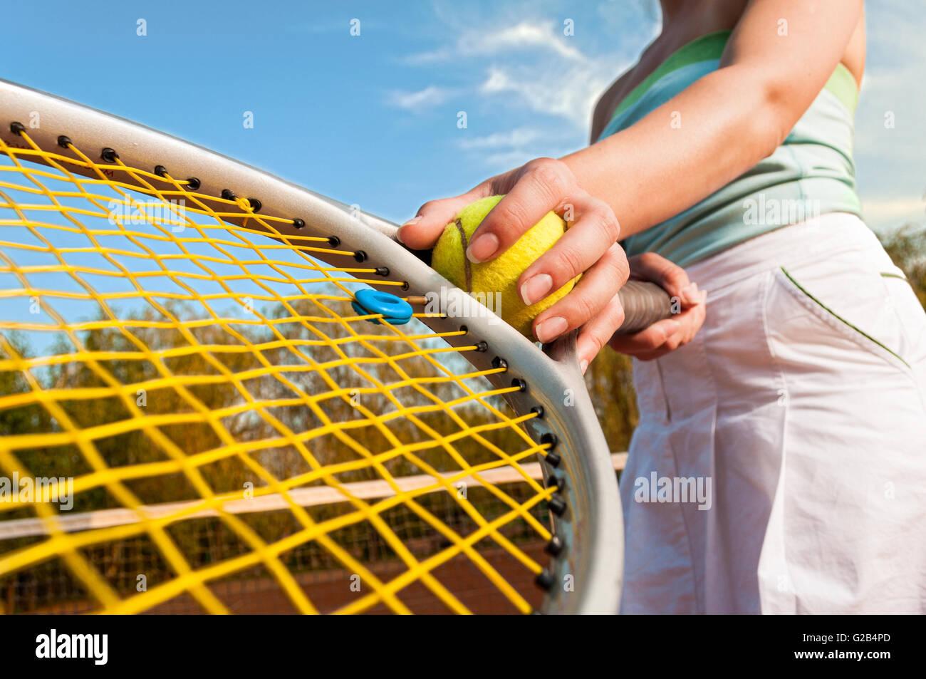 Dinamica concetto di tennis con lettore femmina mano che tiene la sfera e la racchetta Immagini Stock